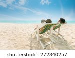 Couple Sunbathing On A Beach...
