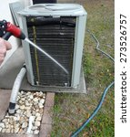 Small photo of Man spraying insect repellant on evaporator coils to prevent nesting and feeding ants from damaging the contactor of air conditioner heat pump unit.