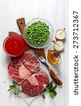 Small photo of Raw fresh cross cut veal shank and Ingredients for making Osso Buco wooden background