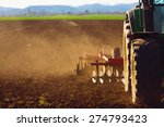 Tractor In Sunset Plowing The...
