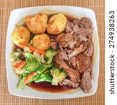 Small photo of Sunday lunch meal of roast lamb, roast potatoes, gravy and vegatables on a white plate from above.
