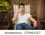 Small photo of Handsome dark haired young man wearing a v-neck white T-shirt while smoking a cigarette in a balcony sitting on chair, in summer