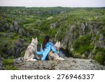 Girl Sitting With Sled Dogs In...