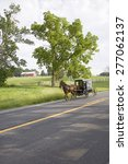 Small photo of Amish horse and carriage driving past barn in Lancaster County, Pennsylvania