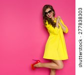 Stock photo crazy about new shoes excited girl in yellow mini dress posing on one leg against pink background 277838303