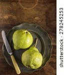 Small photo of Fresh green pears on a pewter plate with a vintage knife, placed on a distressed wood table, photographed from above.