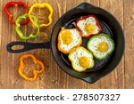 Small photo of Large cast iron skillet with fried eggs in green, yellow, red and orange bell peppers sitting on wooden table with pepper slices