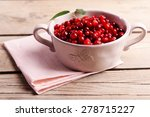 red currant in bowl on wooden