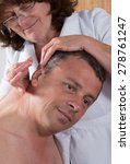 Small photo of Woman acupuncturist prepares to tap needle around ears of man