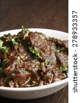 Small photo of kasha mangsho, a curry of goat-meat chunks, mostly boneless, in a rich onion gravy.
