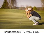 Woman golf player crouching and ...
