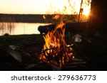 Camp Fire On River Bank An...