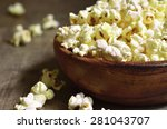 A Bowl Of Popcorn On A Wooden...