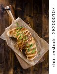 Small photo of Grilled chicken breast on dark wooden background