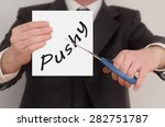Small photo of Pushy, man in suit cutting text on paper with scissors