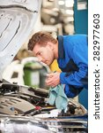 mechanic examining car.... | Shutterstock . vector #282977603