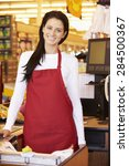 Small photo of Female Cashier At Supermarket Checkout