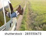 Small photo of Carefree travel woman legs sticking out of window car