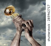 gold cup in dirty hands on sky... | Shutterstock . vector #285962717
