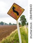 Small photo of Traffic signs ahead of the curve, which pole is tilted on the arid countryside of Thailand.