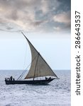 Small photo of traditional african dhow sailing vessel with full sail to the wind and all hands on deck