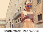 Small photo of Young female tourist checking out the sights while reading a map, gorgeous woman holding a map while touring abroad, stylish hipster studying a map while standing in urban setting in summer, filter