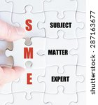 Small photo of Hand of a business man completing the puzzle with the last missing piece.Concept image of Business Acronym SME as Subject Matter Expert
