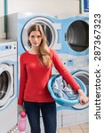 Small photo of female student holding her linen and laundry in launderette, looking at camera