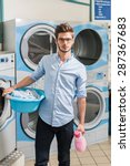 Small photo of looking at camera, young man holding a laundry basket in launderette
