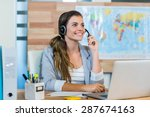 Small photo of Pretty travel agent speaking to customer in the office