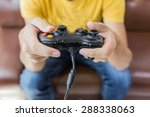 Small photo of An Asian young man holding game controller playing video games
