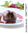 Small photo of Chocolate fondant with strawberries on white plate, closeup