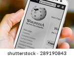 Small photo of LVIV, UKRAINE - May 19, 2015: Hand holding white Samsung Smart Phone with Wikipedia main page screen