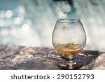 Small photo of Amber alcoholic drink poured in glass stnading on stone rim of fountain on water splashes background copyspace, horizontal picture