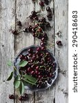 Small photo of Cherries on a pewter plate on wooden background