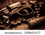 Small photo of Revolver with cartridges and a rosary with cuban cigar on the wooden table. Focus on the cuban cigar. Close up view, image vignetting and the yellow-orange toning