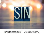 Small photo of The word SIN written in vintage metal letterpress type on a soft backlit background.