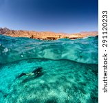 Small photo of Split shot of the diver swimming underwater and desert coast of the South Sinai above the surface, Egypt