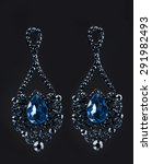 Small photo of earring with colorful blue gems on black background