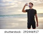 Stock photo young man looking fit and sporty drinking from his water bottle while enjoying a morning run on the 292446917