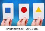 Hands hold up simple shapes on flash cards - stock photo