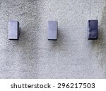 Small photo of Three boxlike light fixtures mounted on exterior weathered concrete wall with rough texture on university campus, with copy space above and below, for themes of industrial or institutional minimalism
