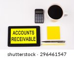 Small photo of Business Term / Business Phrase on Tablet PC with a cup of coffee, Pens, Calculator, and yellow note pad on a White Background - Black Word(s) on a yellow background - Accounts Receivable
