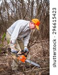 Small photo of Lumberjack logger worker cutting firewood timber tree in forest with chainsaw