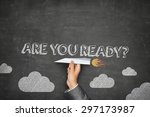 Small photo of Are you ready concept on black blackboard with businessman hand holding paper plane