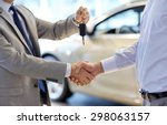 Small photo of auto business, car sale, deal, gesture and people concept - close up of dealer giving key to new owner and shaking hands in auto show or salon