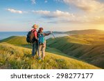 Stock photo hiking couple hikers with backpacks standing on mountain and enjoying sunrise 298277177