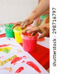 Small photo of Child dipping fingers in washable, non-toxic finger paints, painting a drawing. Sensory play, innovative learning and creativity, fun childhood concept.