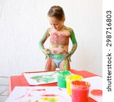 Small photo of Little girl body painting herself with non-toxic, washable finger paints, having fun with creative playing. Sensory play, permissive upbringing, fun childhood concept.