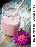 Small photo of Healthy mixed berry smoothie milkshake made from blended blueberries, strawberries and red berries with yogurt. Served in a jug style glass with a stripey straw.